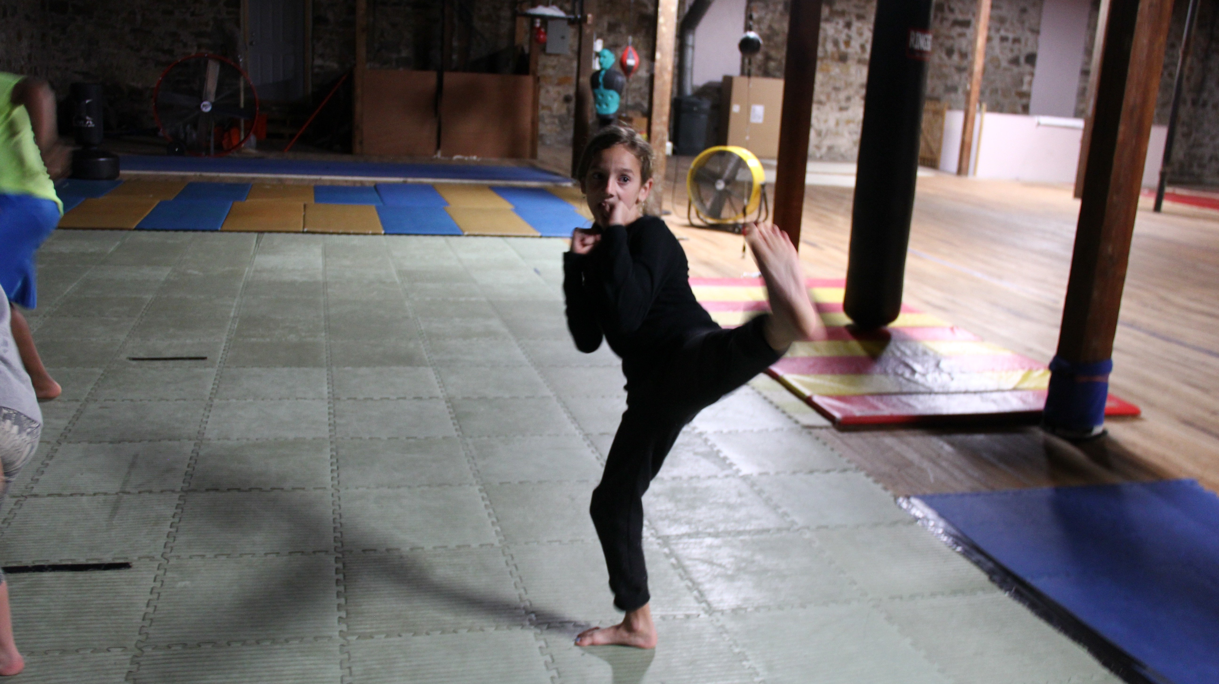 A young student at Harjo Martial Arts in Holdenville throws a kick during practice.